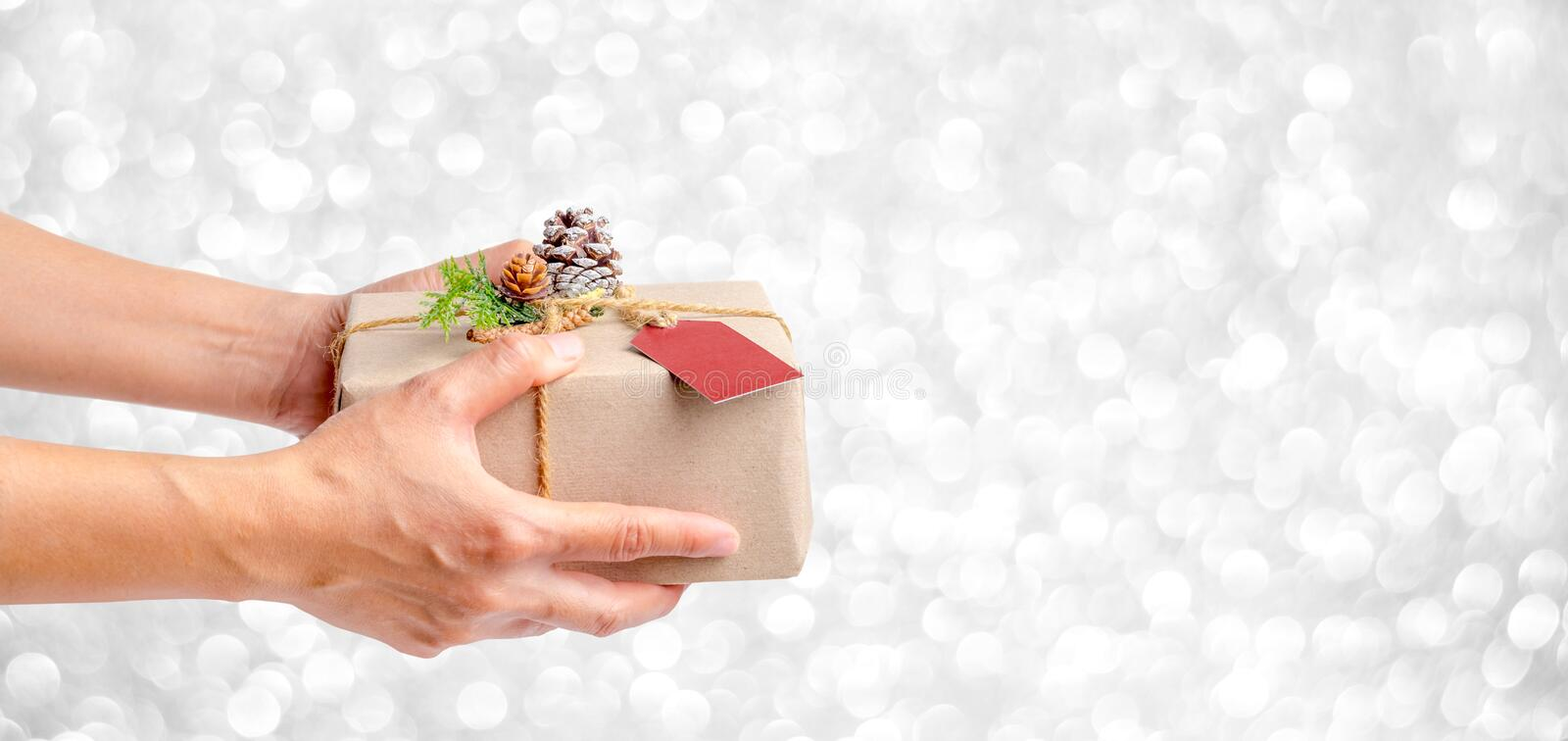 Close up woman hand holding Christmas present box with silver sp royalty free stock images