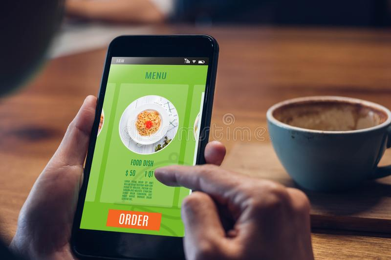 Close up woman hand holding food online mobile apps with hot coffee cup on table sitting at coffee shop,online order concept stock photography