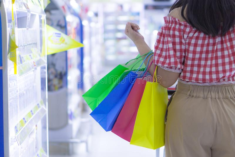 Close up woman hand holding many shopping bags in the shopping mall. Shopping concept stock photos