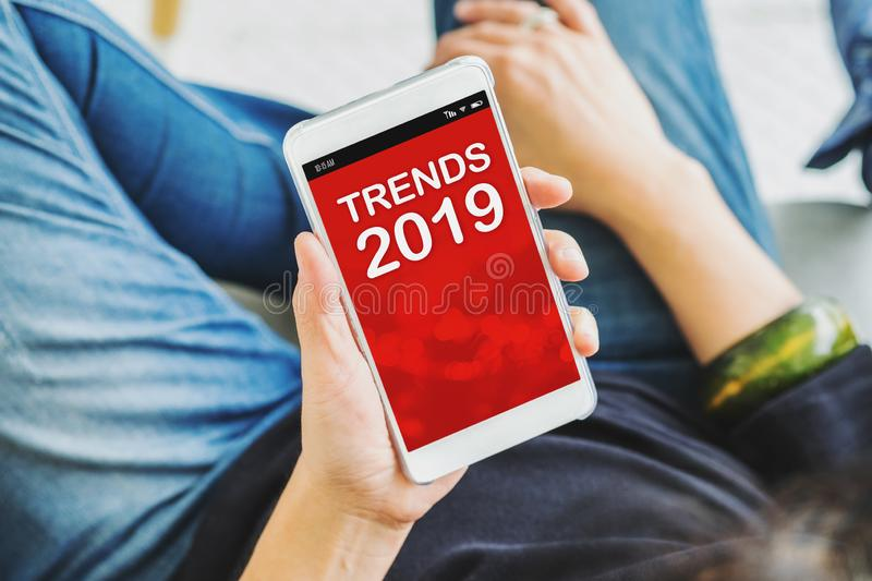 Close up woman hand holding mobile phone with trends 2019 sitting at coffee shop,online digital lifestyle concept.  royalty free stock photo