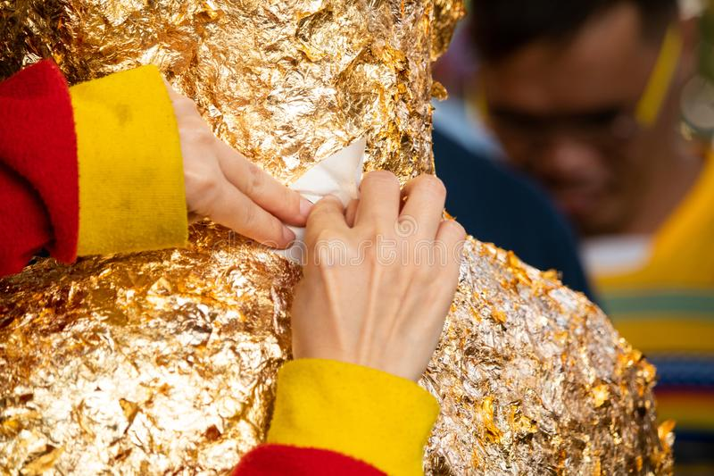 Close-up of woman hand making merit. Gilding gold leaf onto the Buddha stock image