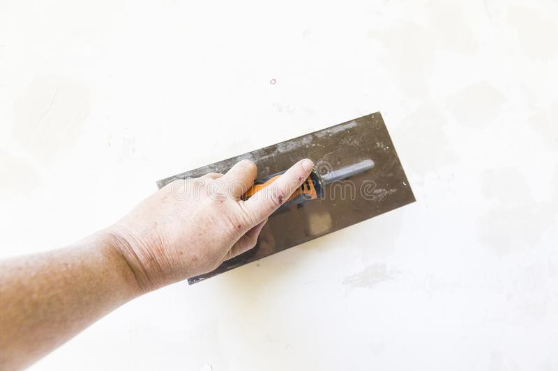 Woman hand with old metal spatula to equalize plaster filler on the wall. Close-up of a woman hand with metal big spatula, to equalize the plaster filler on the stock images
