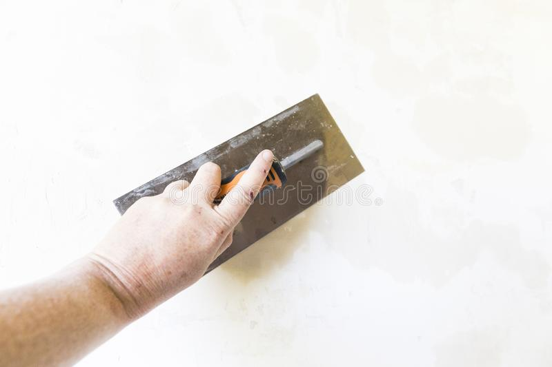 Woman hand with old metal spatula to equalize plaster filler on the wall. Close-up of a woman hand with metal big spatula, to equalize the plaster filler on the royalty free stock image