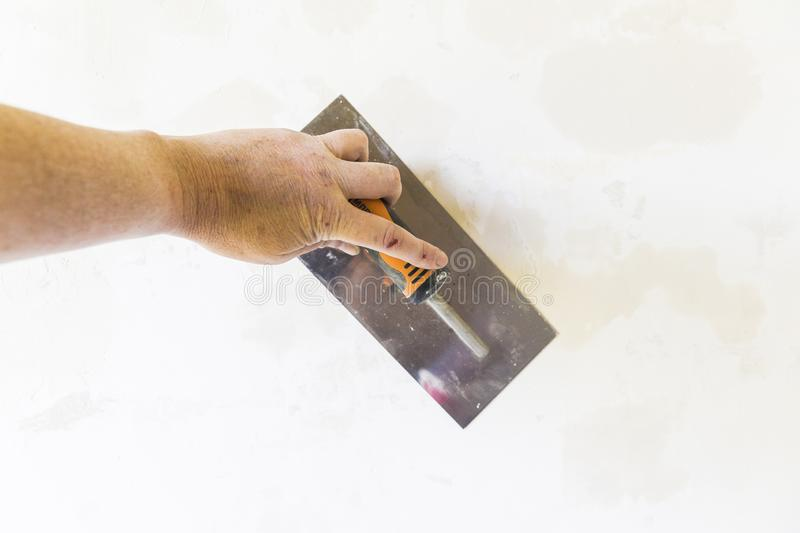 Woman hand with old metal spatula to equalize plaster filler on the wall. Close-up of a woman hand with metal big spatula, to equalize the plaster filler on the royalty free stock photos