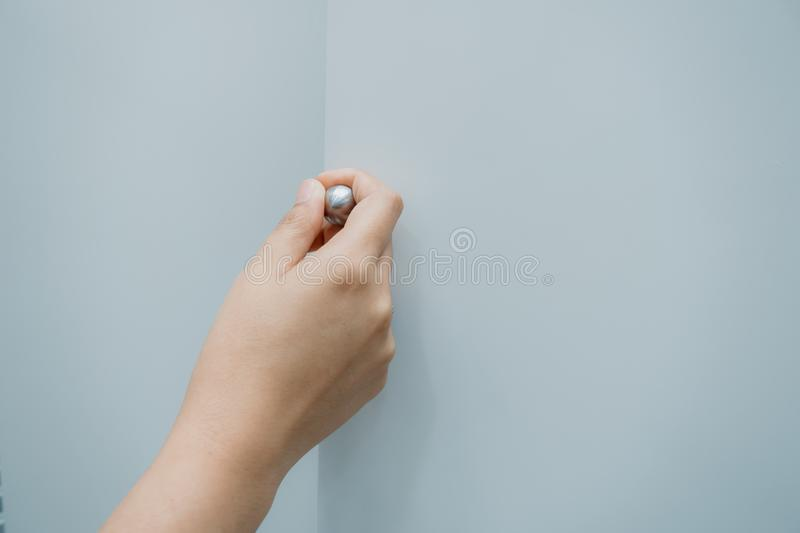 Close-Up of Woman Hand is Opening Door Cabinet in Kitchen Room, Female Hands is Pulling Wooden Door Cupboard in Pantry Room. Furniture Detailing and Household royalty free stock photos