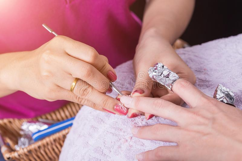 Woman hand while process of manicure in nail shop. Beautiful con stock photo