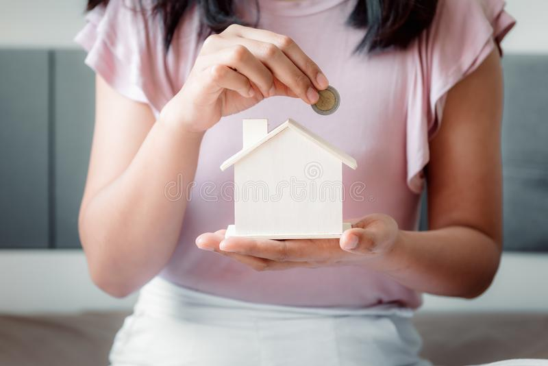 Woman Hand is Putting a Money Coin into Housing for Savings on The Bedroom., Female Hand is Inserting Coin in House Model., Saving. For Finance Future, Business stock image