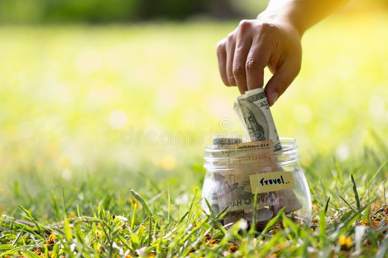Close up woman hand putting, taking out money in glass, jar full stock images