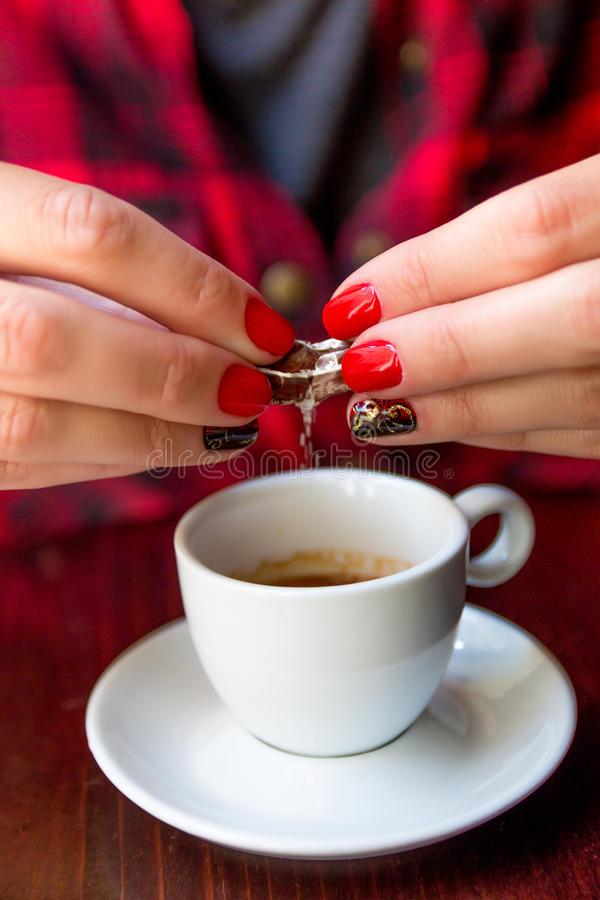 Close up of woman hand with red and black polished nails is drop sugar in an espresso coffee cup at a cafen. Close up of woman hand with red and black polished stock photos