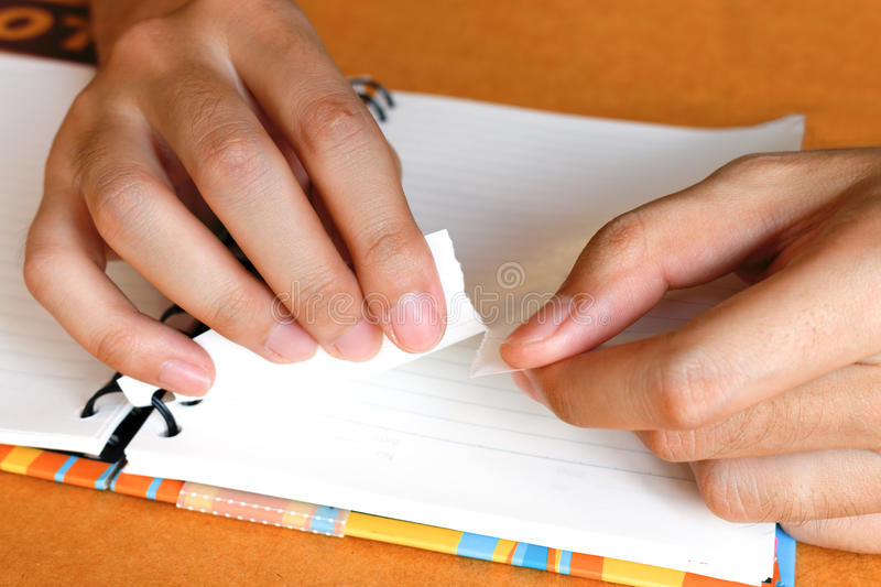 Close up woman hand ripping or tear white paper at notebook stock photos