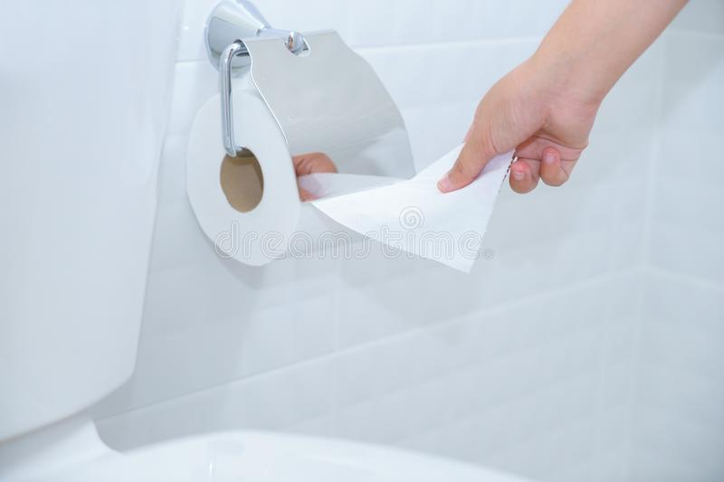 Close up of A woman hand using toilet paper in white and clean t stock photo