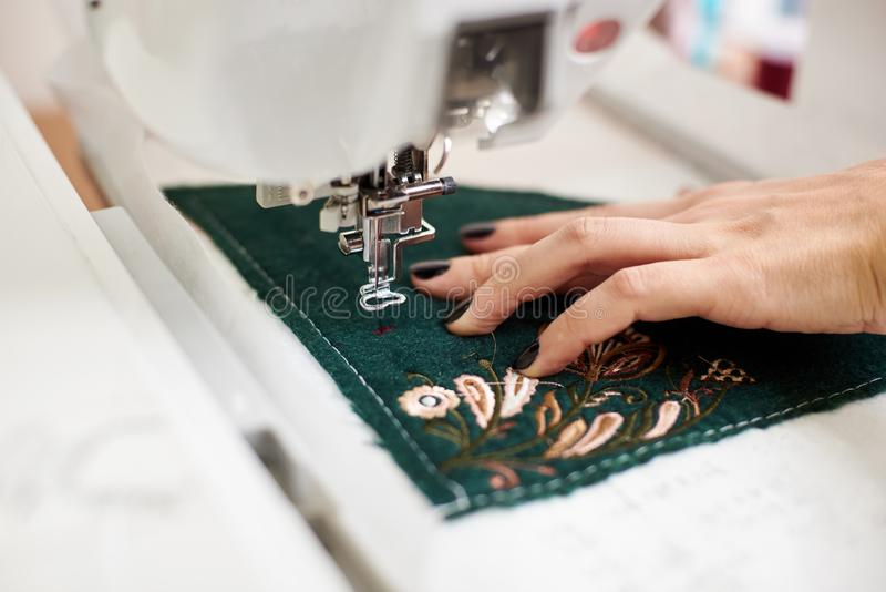 Close-up of woman hand working on sewing machine creating colorful floral pattern on textile detail. stock images