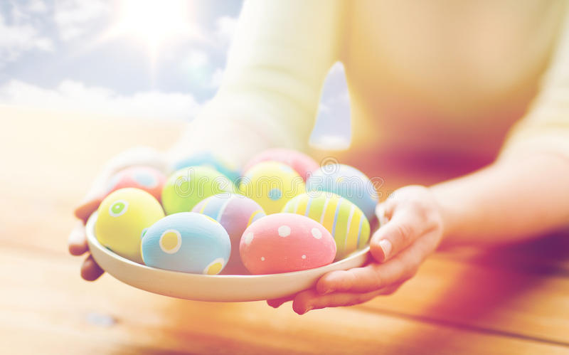Close up of woman hands with colored easter eggs. Holidays, tradition and people concept - close up of woman hands holding colored easter eggs on plate over blue royalty free stock images