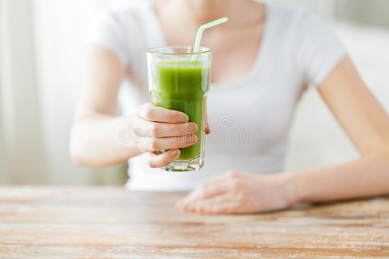 Close up of woman hands with green juice stock images