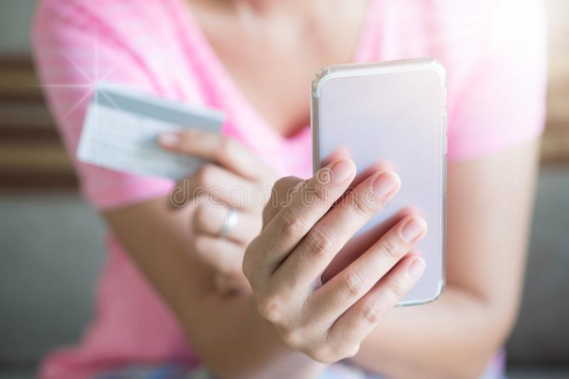 Close up woman hands holding credit card and using cell phone for online shopping on sofa in the living room of the house. stock photography