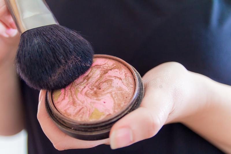 Close up of woman hands holding makeup bronzer.  royalty free stock image