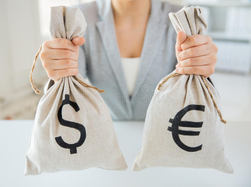 Close up of woman hands holding money bags. Business, finance, saving, banking and people concept - close up of woman hands holding dollar and euro money bags royalty free stock photography