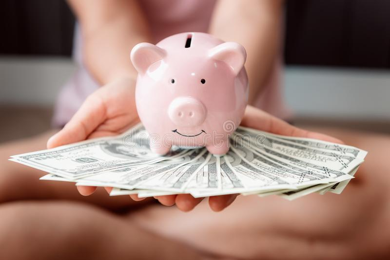 Close-Up Woman Hands is Holding Money Cash and Piggy Bank in Her Bedroom, Pink Piggy Saving, Business Banking and Financial stock images