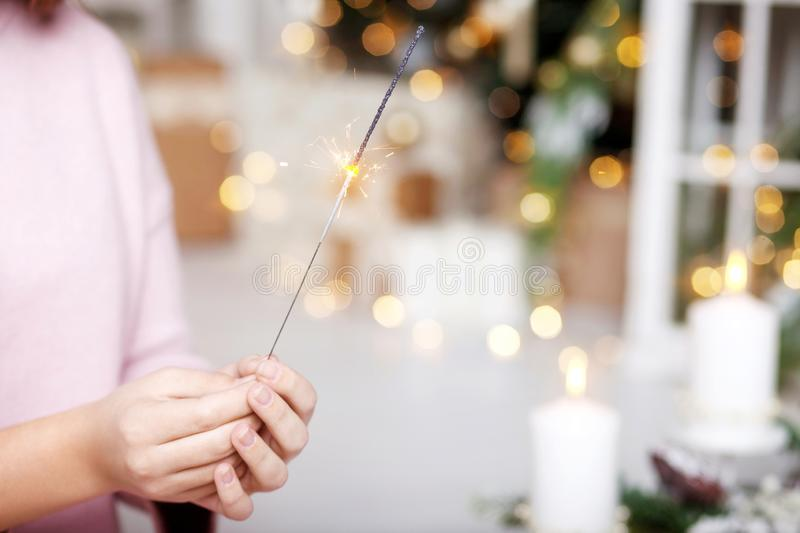 Close up of woman hands holding sparkler. New year party burning sparkler closeup in female hand. Christmas light royalty free stock photography