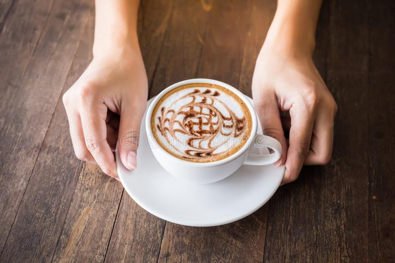 Close up of woman hands holding white cup of coffee with beautiful pattern art and wooden tray on wooden table royalty free stock photo