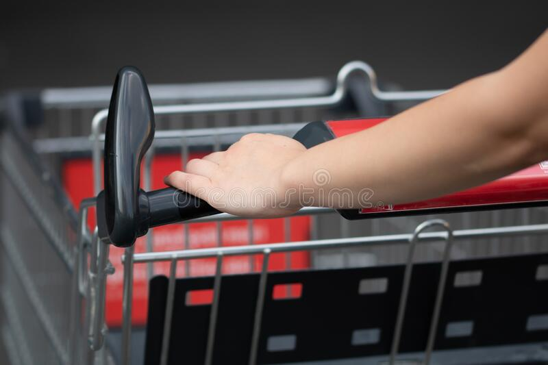 Close up of woman hands pushing empty shopping cart isolated in Bucharest, Romania, 2020 royalty free stock image