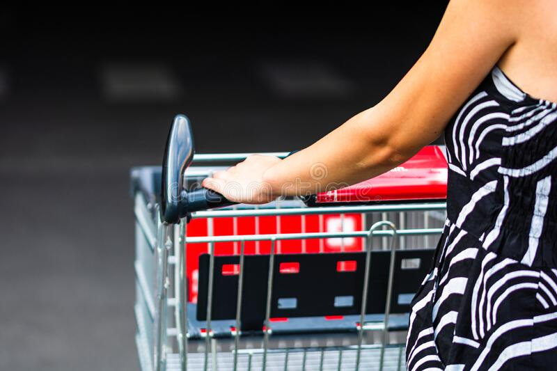 Close up of woman hands pushing empty shopping cart isolated in Bucharest, Romania, 2020 stock image