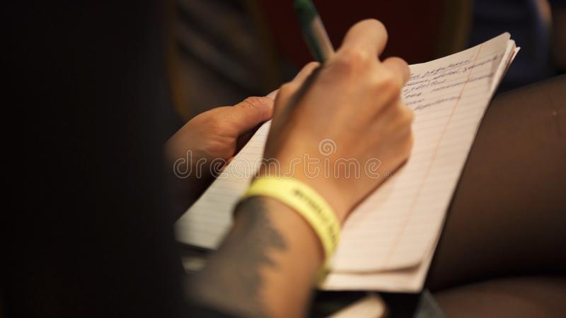 Close-up of woman hands taking notes in conference hall during business presentation. Art. Business meeting royalty free stock image