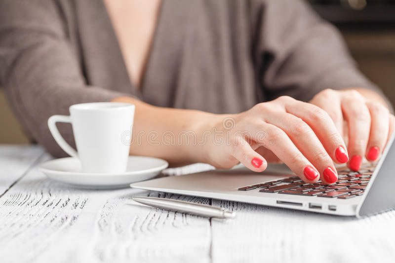 Close up of a woman hands typing in a laptop in a coffee shop te stock image