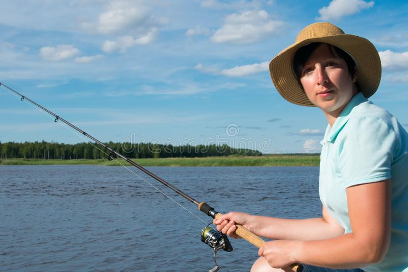 Close-up, a woman with a hat, against a background of a lake, holds a fishing pole to catch a fish royalty free stock images