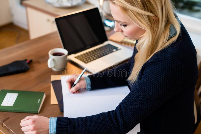 Woman working at her desk stock images
