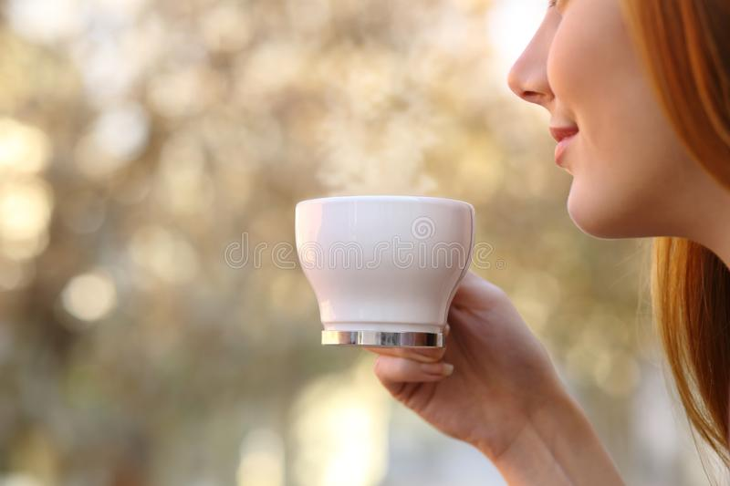 Close up of a woman holding a coffee cup. With a blur warm background stock photo