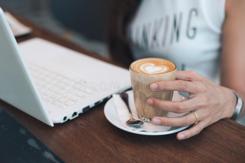 Close-up of Woman Holding Coffee Cup on Table royalty free stock image