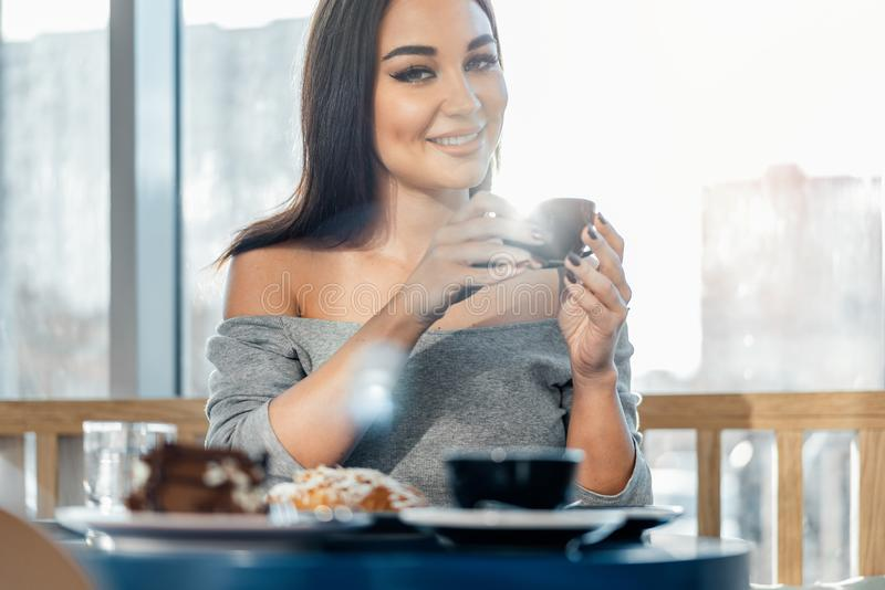 Close up of woman holding cup of coffee, smiling and looking at camera. Front view royalty free stock images