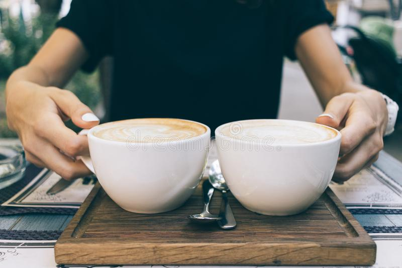 Close-up of a woman holding hands two cups of coffee. In a cafe royalty free stock photo