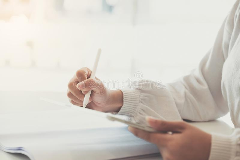 Close up of Woman holding new version digital tablet device in hands with smart pencil.  royalty free stock photos