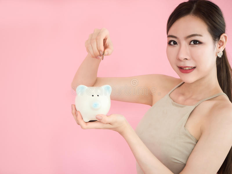 close-up Woman Holding Piggy Bank,beauty girl saving money ,Putting Coin stock photography