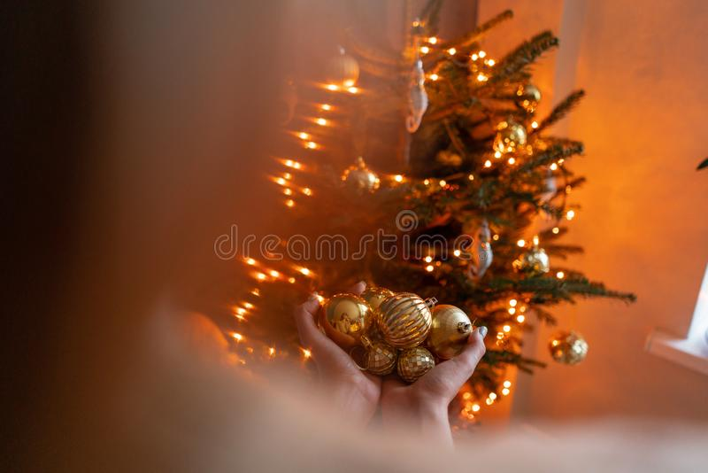 Close-up woman holds in the hands of Golden Christmas tree toys. Winter holidays in a house interior. Golden and white royalty free stock images