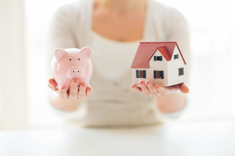 Close up of woman with house model and piggy bank. Building, mortgage, investment, real estate and property concept - close up of woman holding home or house royalty free stock images