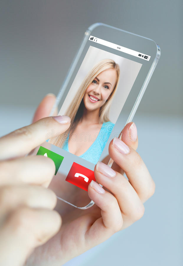 Close up of woman with incoming call on smartphone. Business, technology and people concept - close up of women hand holding and showing transparent smartphone royalty free stock image