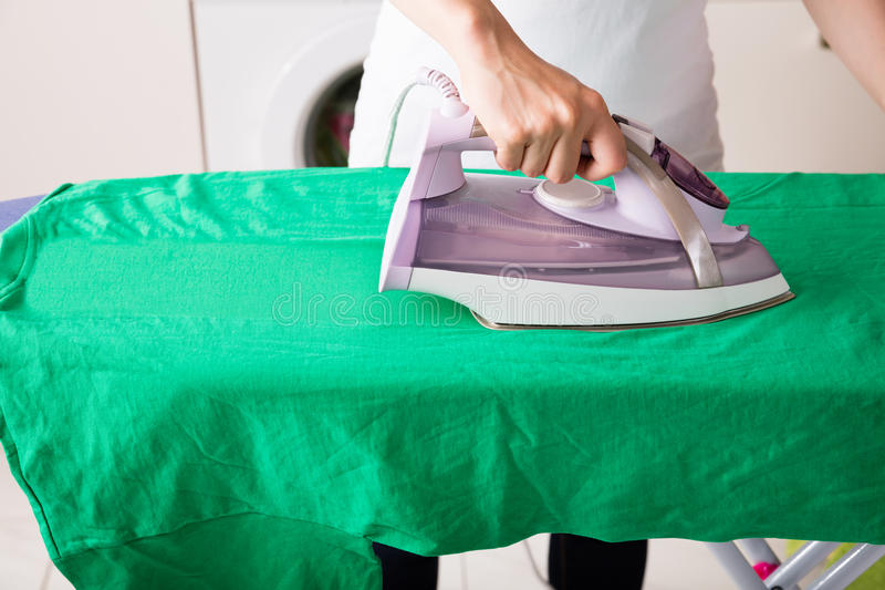Close-up Of Woman Ironing Green T-shirt royalty free stock images