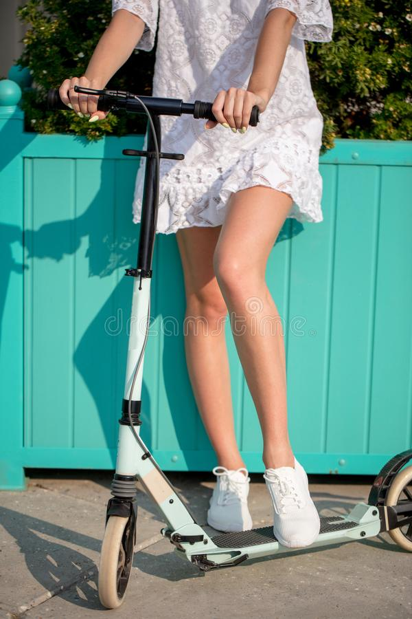 Close up Woman legs on blue kick scooter on road at summer day royalty free stock image