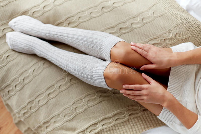 Close up of woman legs in winter knee socks in bed stock images