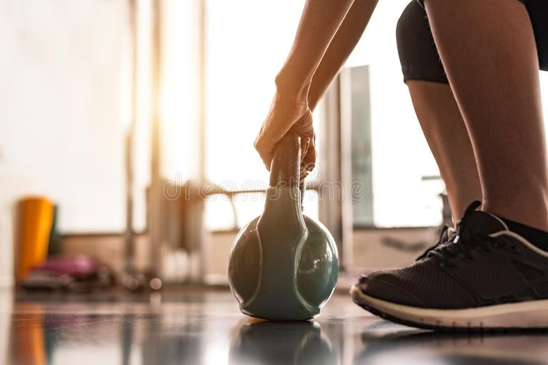 Close up of woman lifting kettlebell like dumbbells in fitness sport club gym training center with sport equipment near window royalty free stock photo