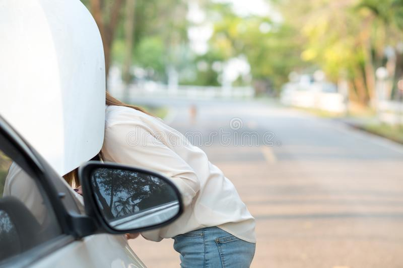 Close up woman looking at her broken down car stock image