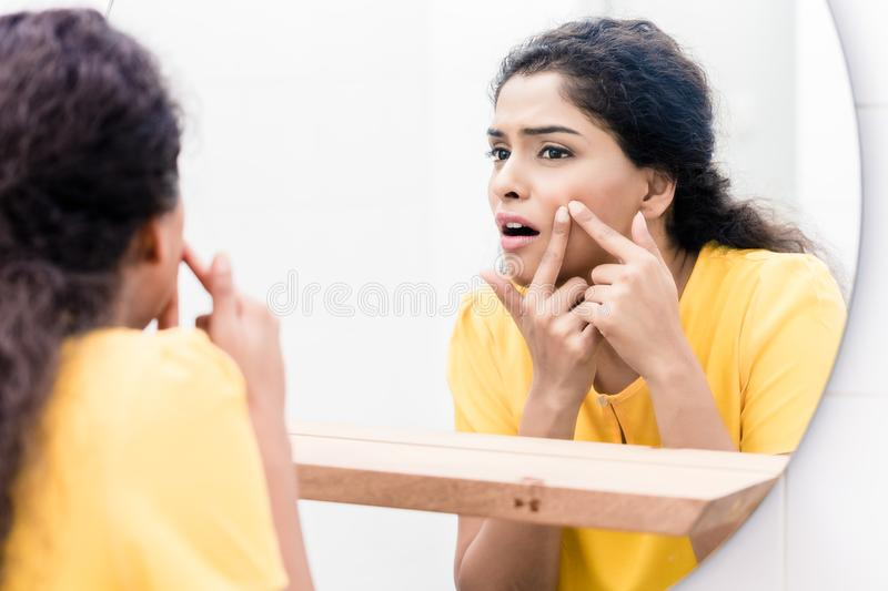 Woman looking in mirror squeezing pimple stock photo