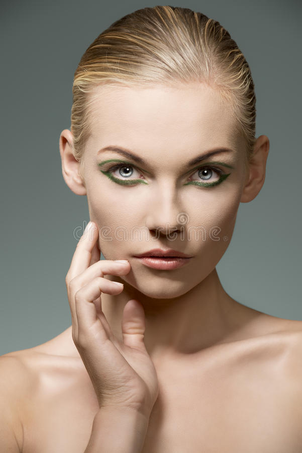 Close-up of woman with make-up. Beauty portrait of sensual blonde girl with pretty green make-up and perfect visage skin. Posing with hand near the face royalty free stock photos
