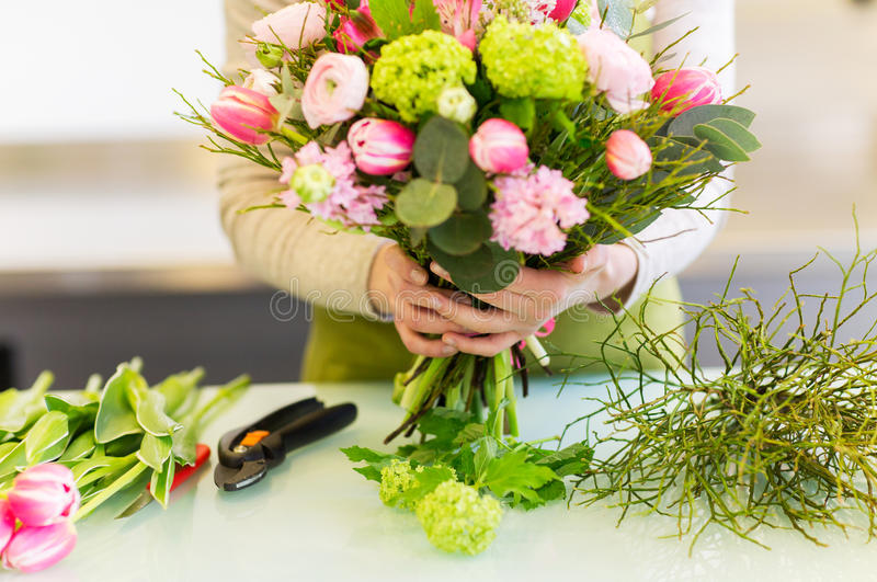 Close up of woman making bunch at flower shop stock image