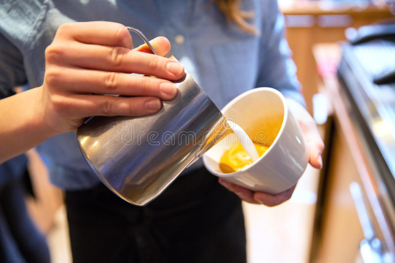 Close up of woman making coffee at shop or cafe. Equipment, coffee shop, people and technology concept - close up of woman pouring cream to cup of coffee at cafe royalty free stock photo