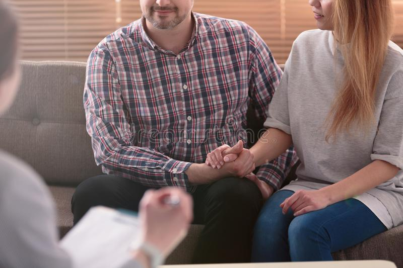 Close-up of woman and man holding hands on a couch during a psychotherapy session. Couples therapy concept. Close-up of women and men holding hands on a couch stock image