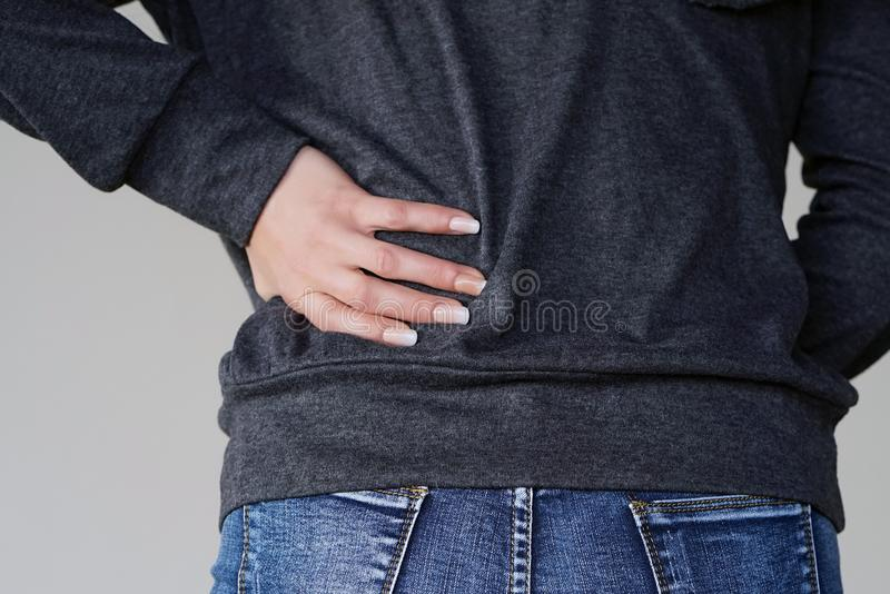 Woman, pain at lower back. Close-up woman with pain in kidneys on gray background. Woman with back ache clasping her hand to her lower back. Woman suffering from royalty free stock photography